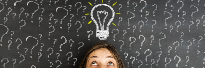 A person surrounded by question marks drawn around them and a light bulb drawn above their head